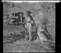 H. H. West holds fish and fishing gear, Mono County vicinity, 1929