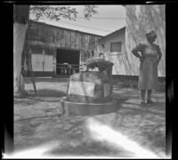 Mertie West drinking from a fountain while Josie Shaw stands nearby, Independence, 1941