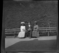 Three unknown persons sitting on a park bench, San Jose, about 1900