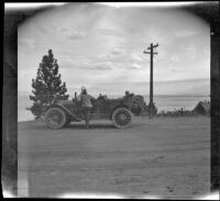 Harry Schmitz and Wilfrid Cline, Jr. stand by H. H. West's Buick at Lake Tahoe, Lake Tahoe, 1917