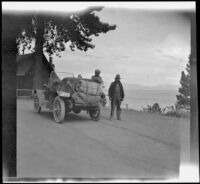 Wilfrid Cline, Jr. and Harry Schmitz stand by H. H. West's Buick at Lake Tahoe, Lake Tahoe, 1917