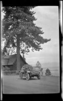 Harry Schmitz stands by H. H. West's Buick on the bank of Lake Tahoe, Lake Tahoe, 1917