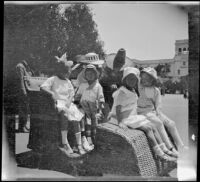Frances Cline, Chester Schmitz, Kate Schmitz, Irene Schmitz and Frances West riding an Osborn Electriquette in Balboa Park, San Diego, [about 1915]