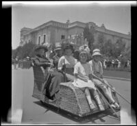 Christina Schmitz, H. H. West, Minnie West, Frances Cline and Elizabeth West riding an Osborn Electriquette along El Prado in Balboa Park, San Diego, [about 1915]