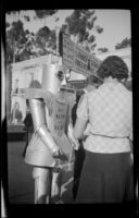 Robot advertising for Alpha the Robot while walking through the California Pacific International Exposition near the Cafe of the World, San Diego, [about 1935]
