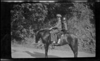 H. H. West, Jr. and another boy posing while riding on horseback, San Dimas, about 1929