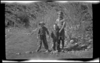 Ambrose Cline, H. H. West, Jr. and Keyo standing alongside a stream, San Francisquito Canyon, about 1923