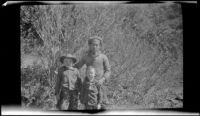 Ambrose Cline, H. H. West, Jr. and Keyo posing in front of tall brush, San Francisquito Canyon, about 1923