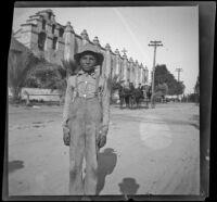Unidentified boy standing outside San Gabriel Mission, San Gabriel, about 1896