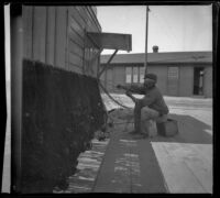 A fisherman mending his net by the station in San Pedro, Los Angeles, about 1898