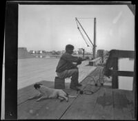 A fisherman mending his net on the wharf in San Pedro, Los Angeles, about 1898
