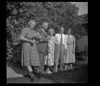 H. H. West's family poses in front of an orange tree by Wayne West's home, Santa Ana, 1941