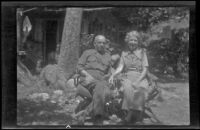 H. H. West and Mertie West sit beneath at tree at Glen Velzy's cabin, San Gabriel Mountains, 1941