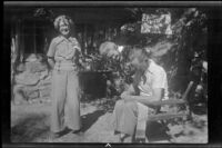 Mertie West poses while Nina Meyers watches Glen Velzy mend the back of his chair, San Gabriel Mountains, 1941