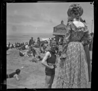 John Duvall and Mary Haas on the beach with the camera obscura in the background, Santa Monica, about 1895