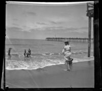 People on the beach with a pier in the background, Santa Monica, about 1895
