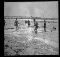 Men play in the surf with the pier in the background, Santa Monica, about 1895