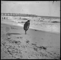 Woman stands on the beach with the pier in the background, Santa Monica, about 1895