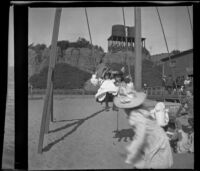 Girls play on a swings with the North Beach Bath House at the right, Santa Monica, about 1895