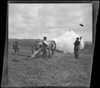 Two servicemen fire a cannon in Los Angeles National Cemetery during Decoration Day while a spectator watches, Los Angeles, about 1895