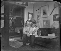 Bob Brain and Aileen Brain sitting on their sofa, Santa Monica, [about 1900]