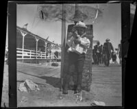 Lester Shaw stands on the boardwalk holding firecrackers, Santa Monica, 1901