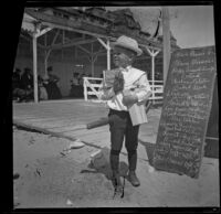 Lester Shaw stands by a chalkboard sign holding firecrackers, Santa Monica, 1901