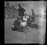 H. H. West sits on the beach with Lester Shaw and William Shaw, Santa Monica, 1901