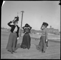 Pinkie Lemberger, Mertie Whitaker and Nella West hold onto their hats while standing on a pier, Santa Monica, about 1900