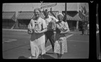 Agnes Whitaker and Mertie West cross a street carrying packages, Bishop, 1940