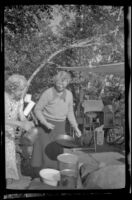 Mertie West and Agnes Whitaker hold pots and pans at their campsite at Rock Creek, Mammoth Lakes vicnity, 1940