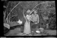 Mertie West touches Agnes Whitaker's hair at a campsite at Rock Creek, Mammoth Lakes vicinity, 1940