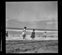 Girls wade through the surf at North Beach, Santa Monica, about 1895