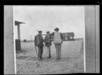 """Frank Siefert, Guy West, and E. C. """"Dick"""" Taylor stand in front of the West's beach cottage holding guns, Venice, about 1903"""