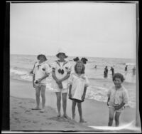 Frances West, Elizabeth West, Irene Schmitz and Chester Schmitz pose at the beach, Venice, [about 1915]