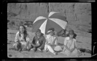 Elizabeth West, Chester Schmitz, Frances West and Irene Schmitz sit in front of a beach umbrella, Santa Monica, [about 1915]