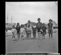 Elizabeth West, Edmond Mead, Frances West and Paul Mead pose with other children on the beach in front of Venice pier, Venice, about 1910