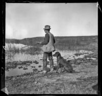 Guy M. West stands with his gun and dog at the edge of Watson Lake, Long Beach vicinity, about 1895