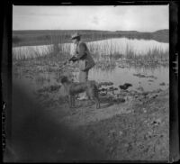 H. H. West stands with his gun and Guy West's dog at the edge of Watson Lake, Long Beach vicinity, about 1895