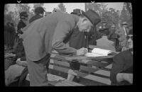 Man writes in a register at the Iowa Picnic in Lincoln Park, Los Angeles, 1939