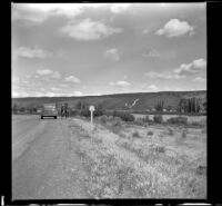 Mertie West and Rex V. Wilson stand on the side of the road alongside the Snake River, Hagerman vicinity, 1942
