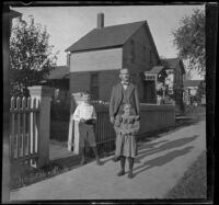 Robert A. Brydolf poses with his children, Vernon and Marvel, outside their home, Aurora, 1900