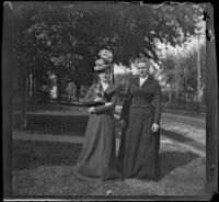 Louise Parsons and Nella A. Brydolf pose on the front lawn with a cat, Burlington, 1900