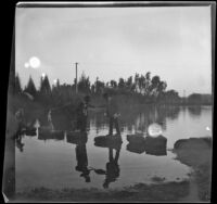 Men helps a woman across the stepping stones at Lincoln (Eastlake) Park as a boy follows behind, Los Angeles, about 1900