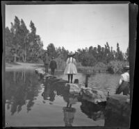 People walk across on stepping stones to cross the lake at Lincoln (Eastlake) Park, Los Angeles, about 1900