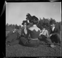 Ben Tyler, Lena Weideman, Mary Dixon, Daisy Connor, and Mr. Weideman sit on the grass in Lincoln (Eastlake) Park, Los Angeles, about 1900