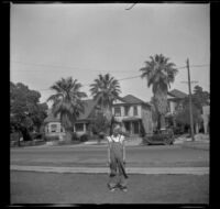 A boy stands on a lawn in front of old Quayle properties on Griffin Avenue between Manitou and Baldwin streets, Los Angeles, 1930