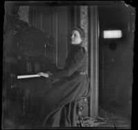 Louise Ambrose sits at the piano in her home, Los Angeles, about 1894
