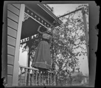 Worm's-eye view of Louise Ambrose balancing on a porch rail, Los Angeles, about 1894