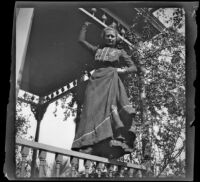 Worm's-eye view of Louise Ambrose posing while standing atop a porch rail, Los Angeles, about 1894